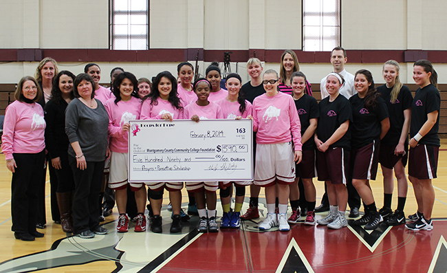 Representatives from MCCC's Foundation join the Mustangs and HACC women's basketball teams for a check presentation at halftime on Feb. 8. Photo by Alana J. Mauger