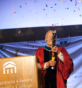 Dr. Lee Bender shoots a confetti cannon following his speech, drawing applause from the crowd. Photo by John Welsh